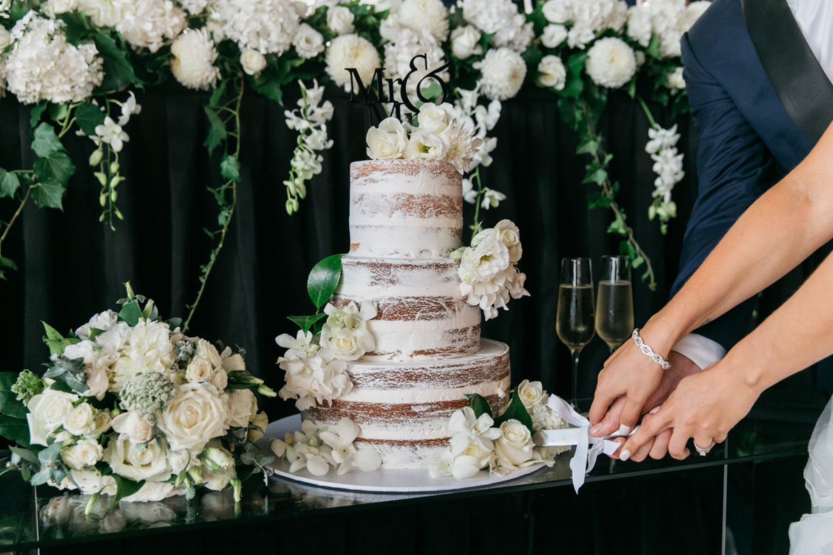 naked three tier wedding cake with white roses and greenery