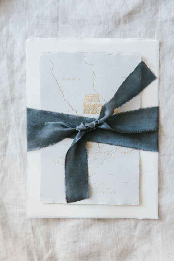ivory textured wedding invitation with blue hand dyed silk ribbon