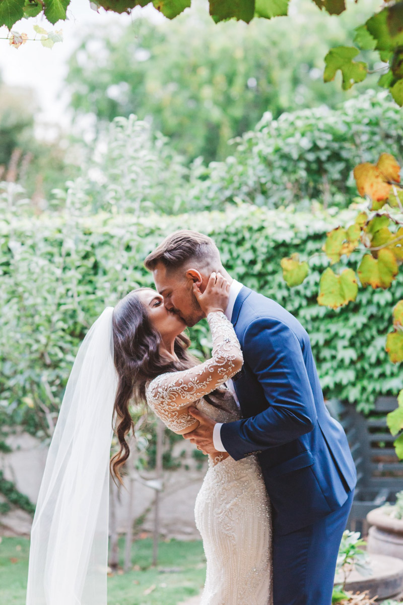 bride and groom kissing - Real bride wears Demetrios Platinum 330 wedding dress