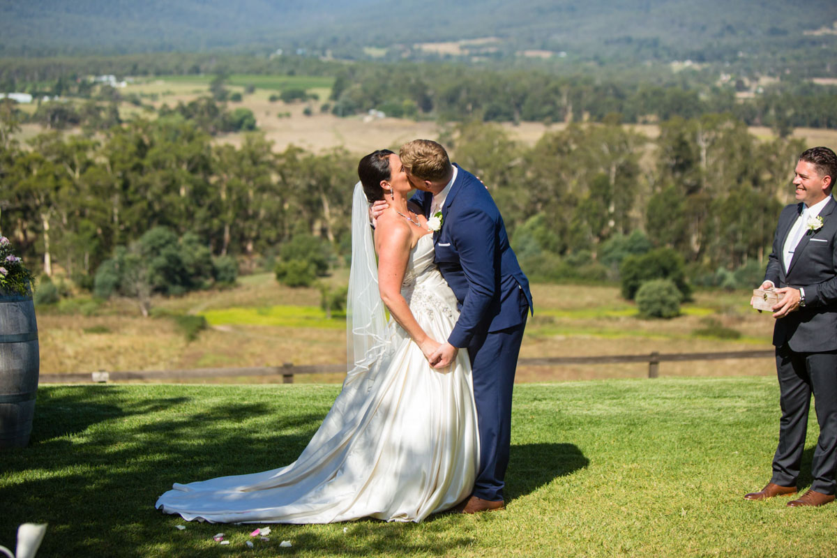 Photo of a bride and groom kissing aisle