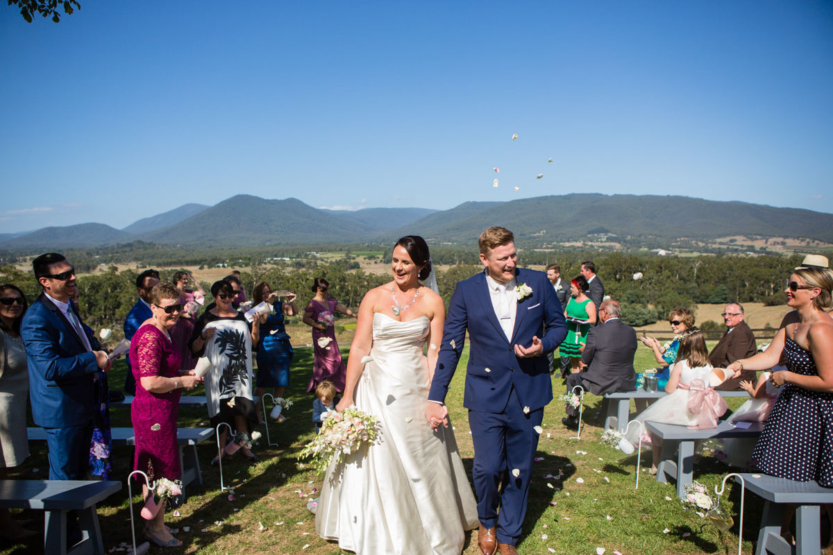 Photo of a bride and groom walking down aisle