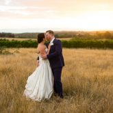 Photo of a bride and groom kissing in a field at sunset