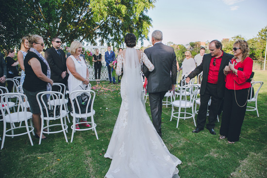 bride walking down aisle with long train wedding dress photo