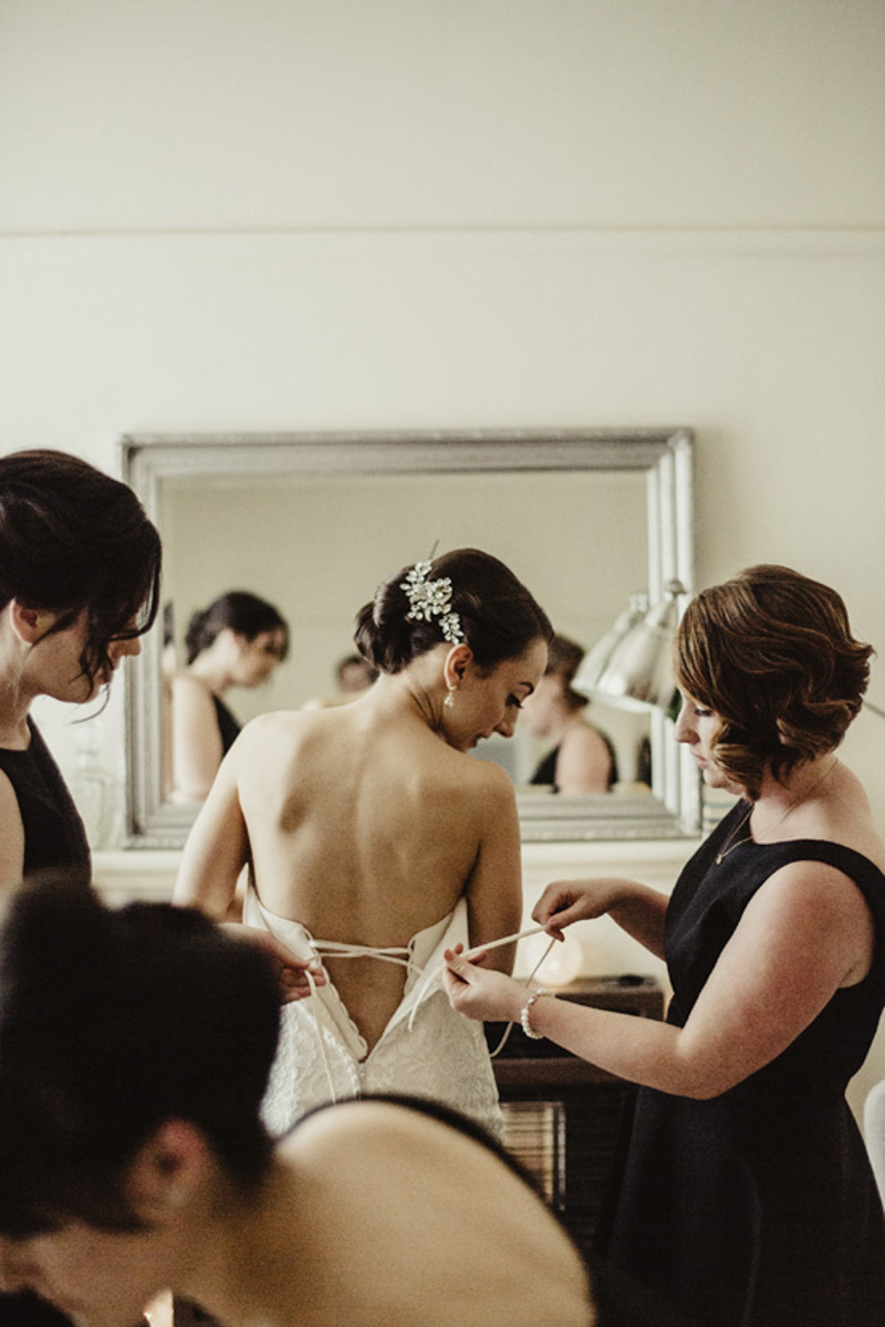 bridesmaids helping bride get ready photo