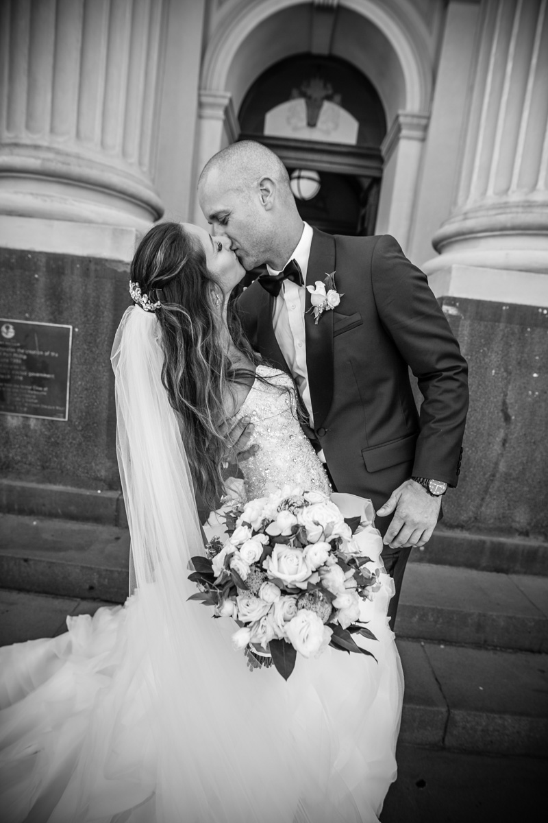 black and white photo bride and groom kissing with veil