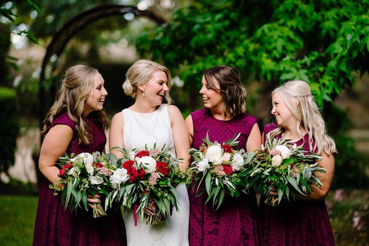 Bride with bridesmaids wearing maroon dresses and ornani wedding dress by Pronovias