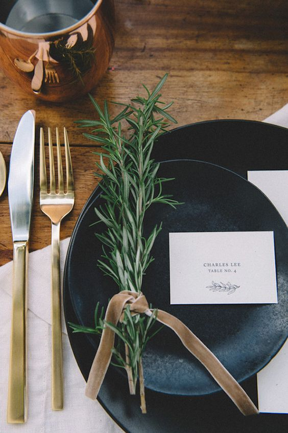 rustic table setting, black plates, gold cutlery and rosmary
