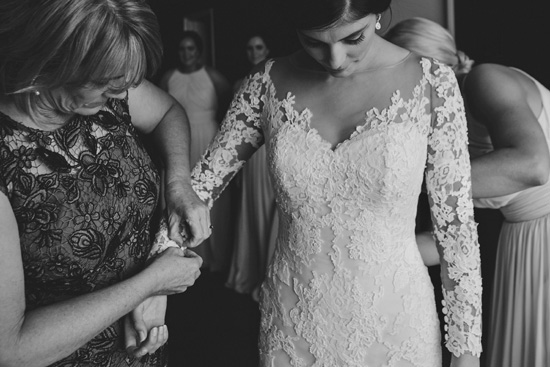 black and white photo bride getting ready wearing off the shoulder lace wedding dress Tibet by Pronovias