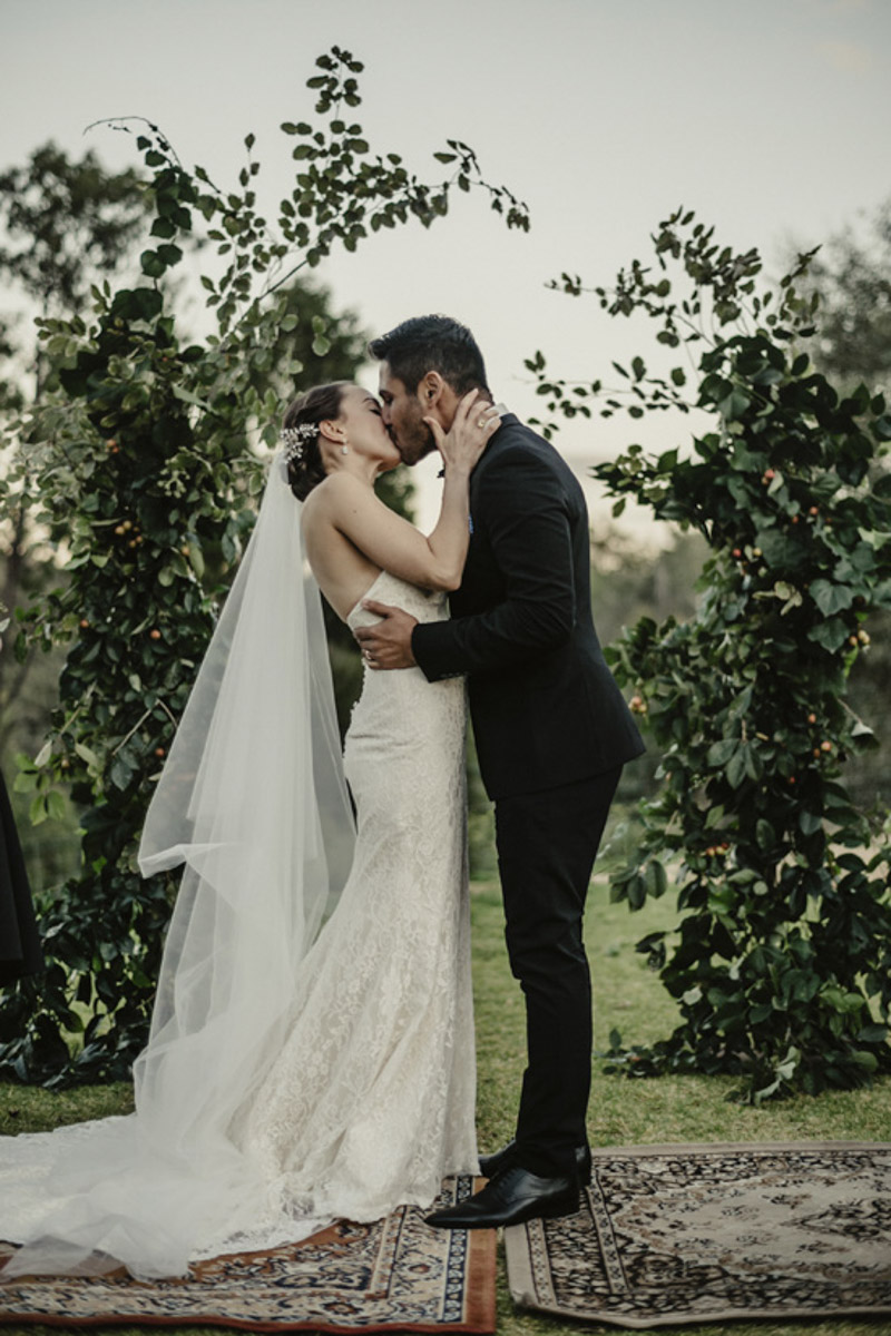 bride and groom kissing ceremony photo under arbour
